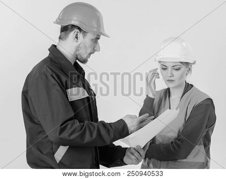 Solving Problems Concept. Man And Woman In Hard Hats, Uniform Looks At Blueprint. Builder And Engine