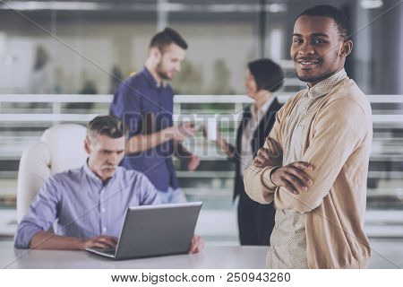 African American With Colleagues In Office. Young Smiling Businessman With Crossed Hands. Business P