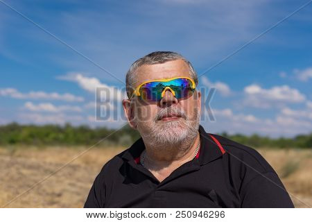 Outdoor Portrait Of A Bearded Senior In Sunglasses Against Blue Cloudy Sky And Agricultural Field. T