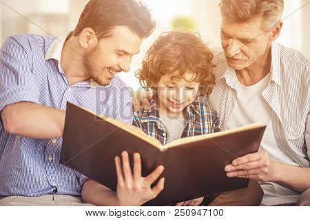 Grandfather Father And Son Reading Book. Generation Portrait. Family Concept. Cheerful Men. Three Ge