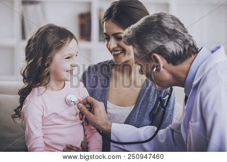 Doctor Examing Patient. Funny Doctor Calms Of Small Patient. Family On Consulation Of Pediatrician.