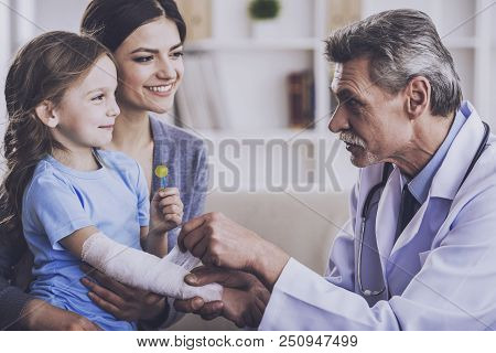 Kindly Doctor Bandages Hand. Doctor Examing Patient. Family On Consulation Of Pediatrician. Healthca
