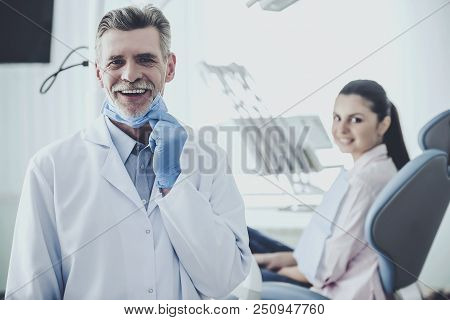 Doctor And Mask After Treatment. Concept Of Patient. Portrait Of Smiling Dentist. Smiling Girl On Ba
