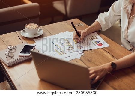 Close Up Of Business Woman Working With Documents And Laptop In Office. Business And Lifestyles Conc