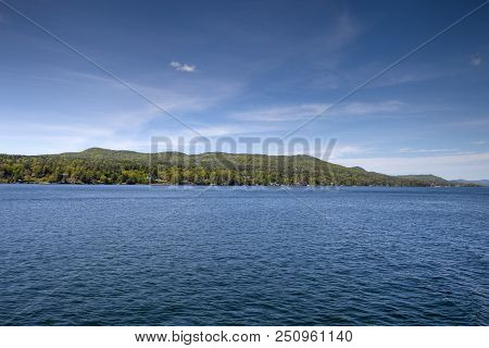The Lush Green Mountains Divide The Beautiful Blue Sky And Water