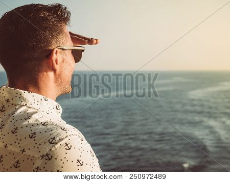 Attractive Man In A White Shirt With Patterns In The Form Of Anchors On The Top Deck Of A Cruise Shi