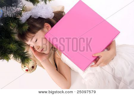 Pretty Little Girl Sleeping Under A Christmas Tree With Present