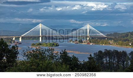 Panoramic View Of The Fraser River And Port Mann Bridge Against The Backdrop Of The The Mountain Rid