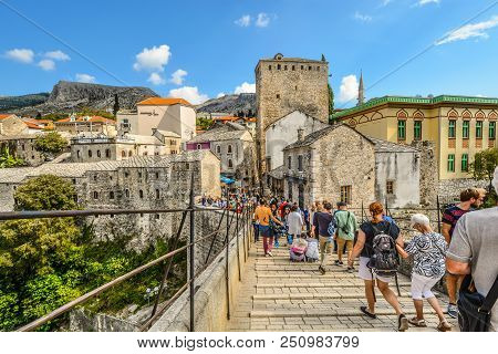 Mostar, Bosnia And Herzegovina - October 1 2017: A Crowd Of Tourists Cross Over The Restored Mostar