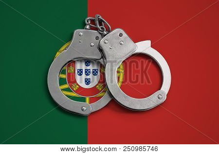 Portugal flag  and police handcuffs. The concept of observance of the law in the country and protection from crime. poster