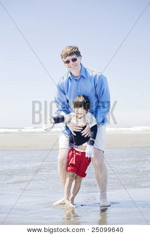 Father Walking Disabled Son At The Beach