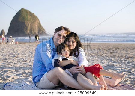 Small Family With Disabled Little Boy Sitting At The Beach By The Ocean