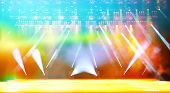 Illuminated empty concert stage with haze and rays of multicolored light. Background for music show poster