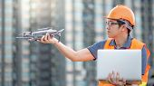 Young Asian man working with drone and laptop computer at construction site. Using unmanned aerial vehicle (UAV) for land and building site survey in civil engineering project. poster