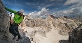 mountain guide on a steep and exposed Via Ferrata in the Dolomites of Alta Badia in Italy poster