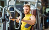 Portrait of a handsome bodybuilder smiling and looking at camera while exercising at a modern fitness machine for pectoral fly and deltoid workout poster