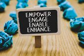 Handwriting text writing Empower Engage Enable Enhance. Concept meaning Empowerment Leadership Motivation Engagement Stand blackboard with white words behind blurry blue paper lobs woody floor poster