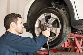 Confident worker using impact wrench on change tire in repair shop poster