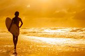 Saturated stylised rear view of beautiful sexy young woman surfer girl in bikini with white surfboard on a beach at sunset or sunrise poster