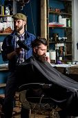 Barber with hairdryer works on hairstyle for bearded man barbershop background. Hipster bearded client getting hairstyle. Barber with hairdryer drying hair of client. Hipster lifestyle concept. poster