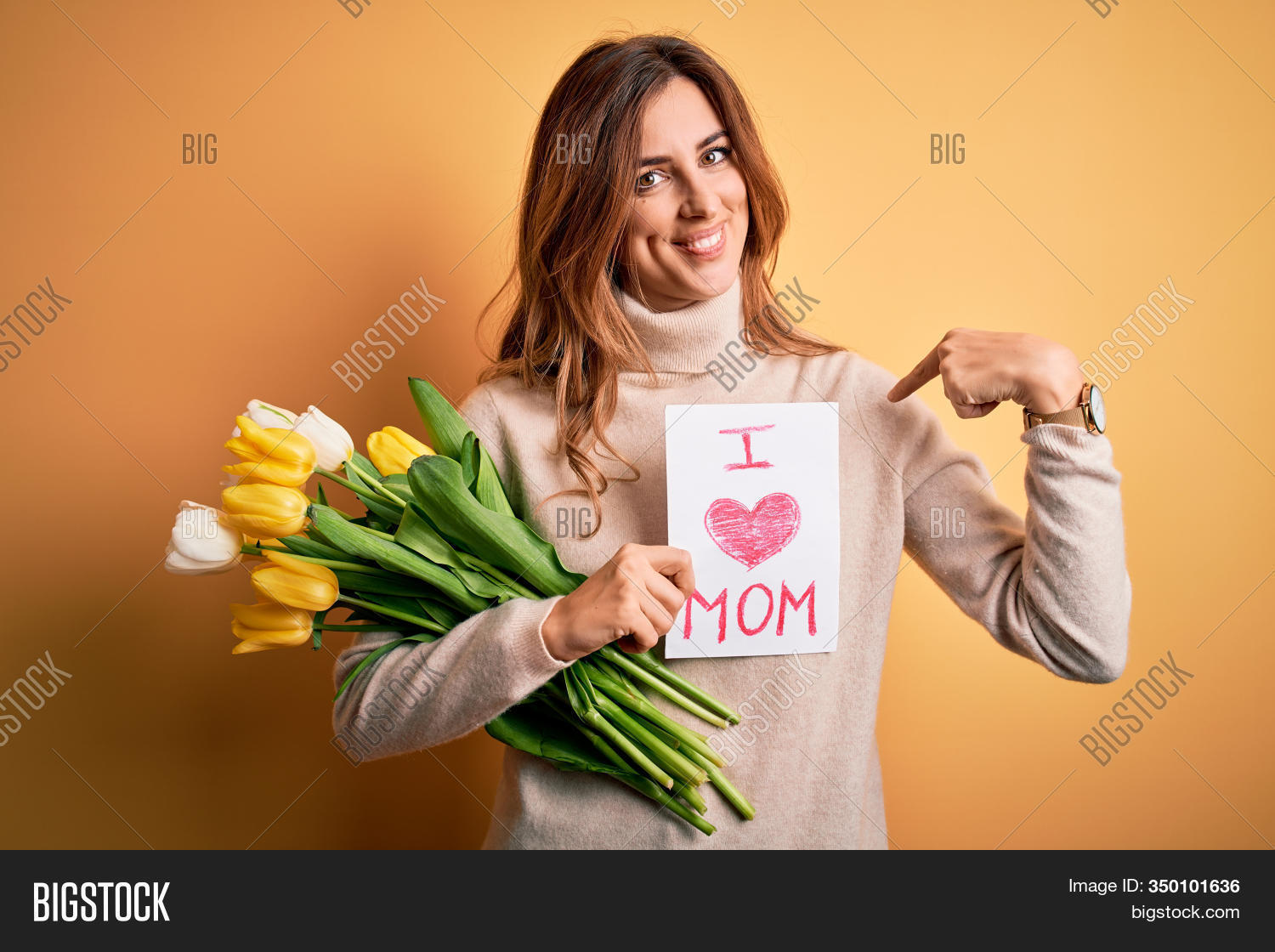 Beautiful brunette woman holding love mom message and tulips celebrating mothers day with surprise face pointing finger to himself