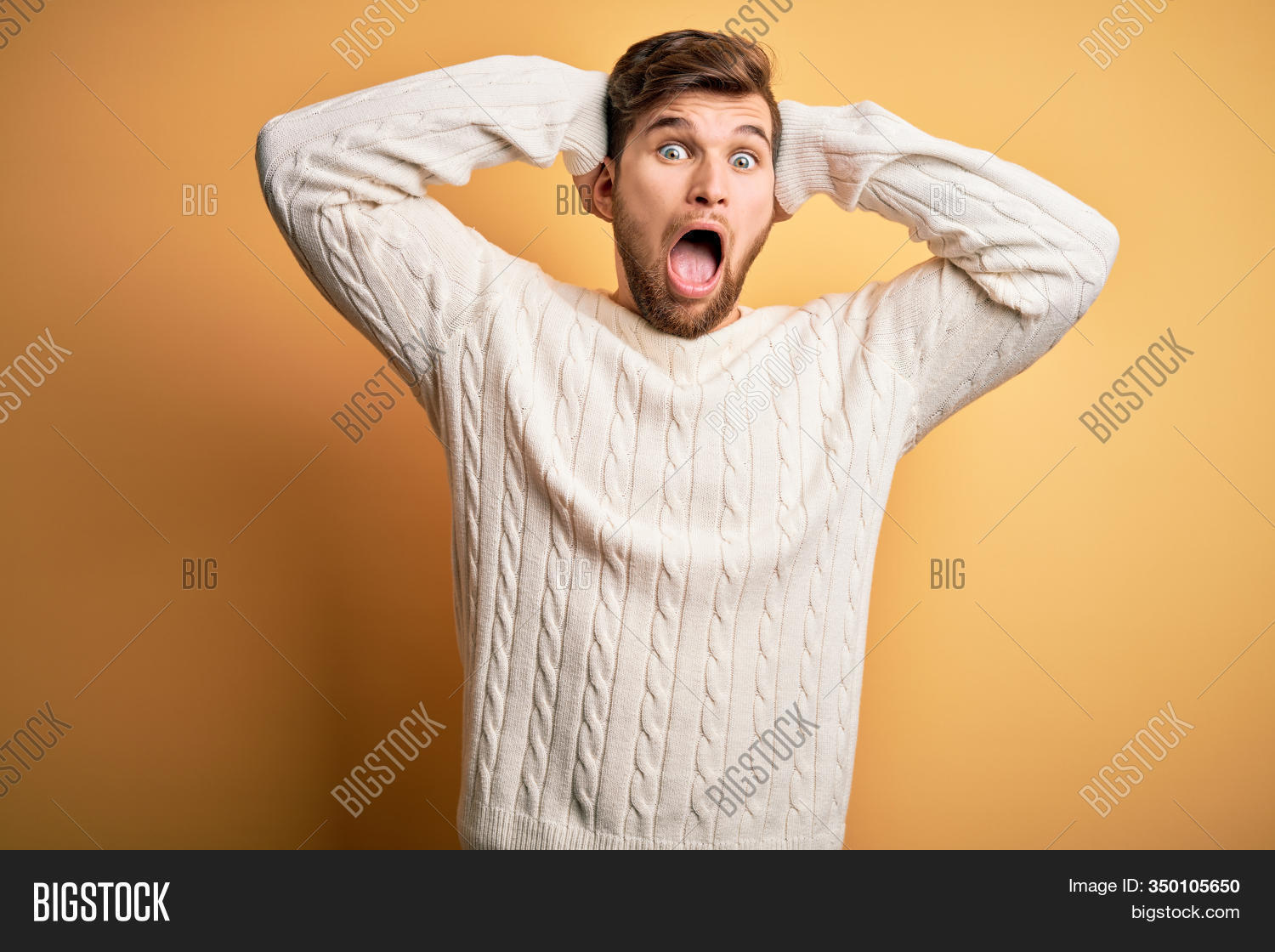 Young blond man with beard and blue eyes wearing white sweater over yellow background Crazy and scared with hands on head, afraid and surprised of shock with open mouth