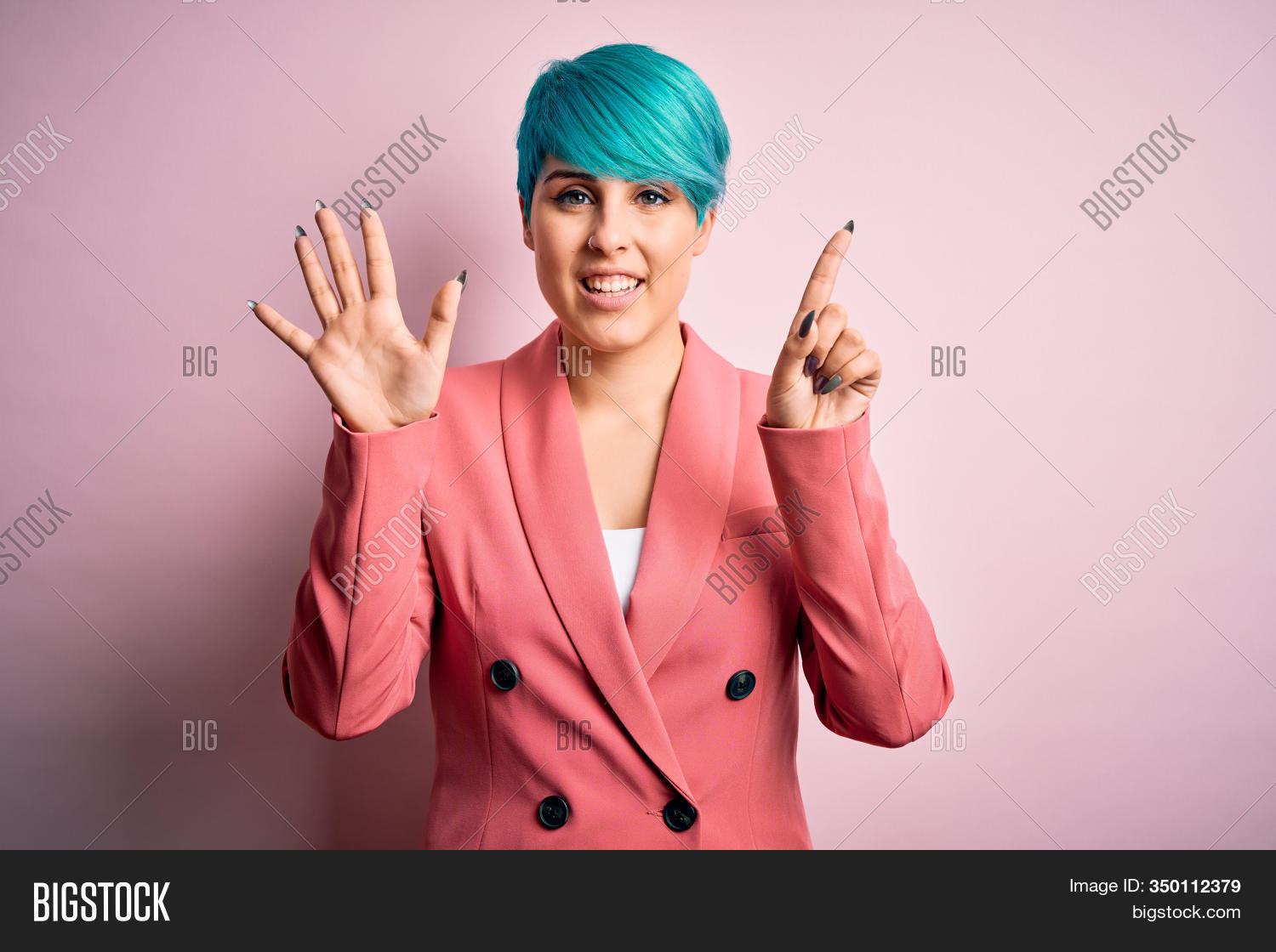 Young beautiful businesswoman with blue fashion hair wearing jacket over pink background showing and pointing up with fingers number six while smiling confident and happy.