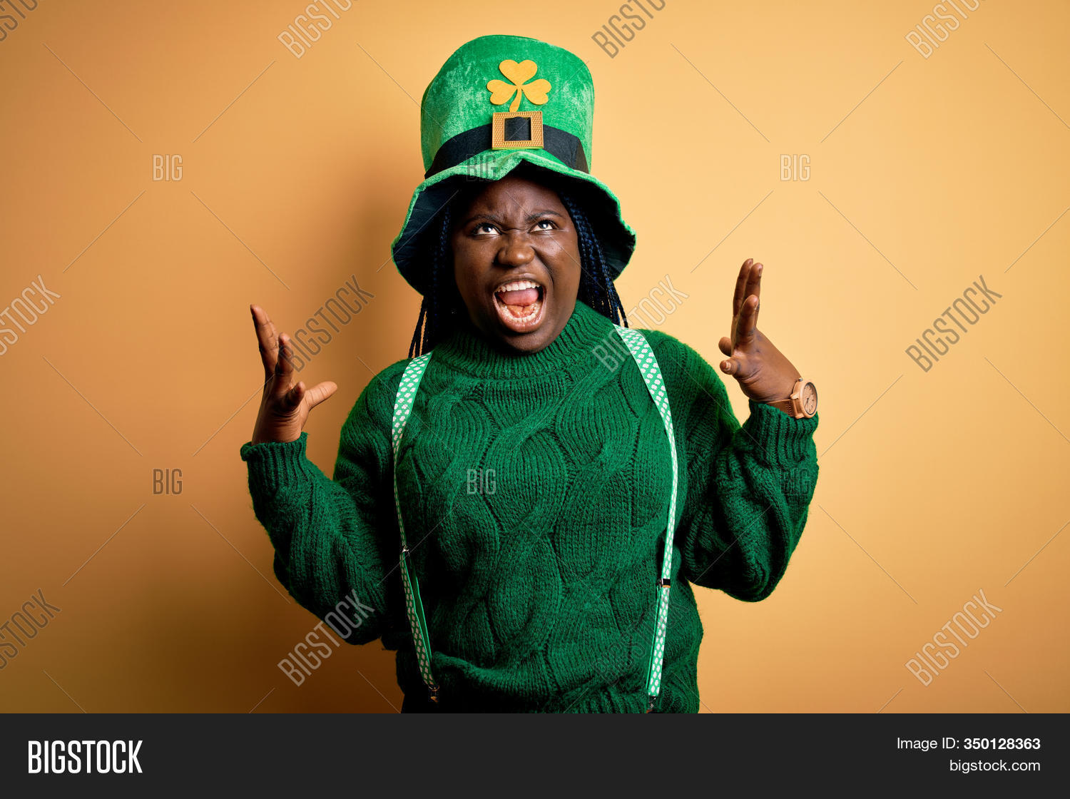 Plus size african american woman with braids wearing green hat with clover on st patricks day crazy and mad shouting and yelling with aggressive expression and arms raised. Frustration concept.