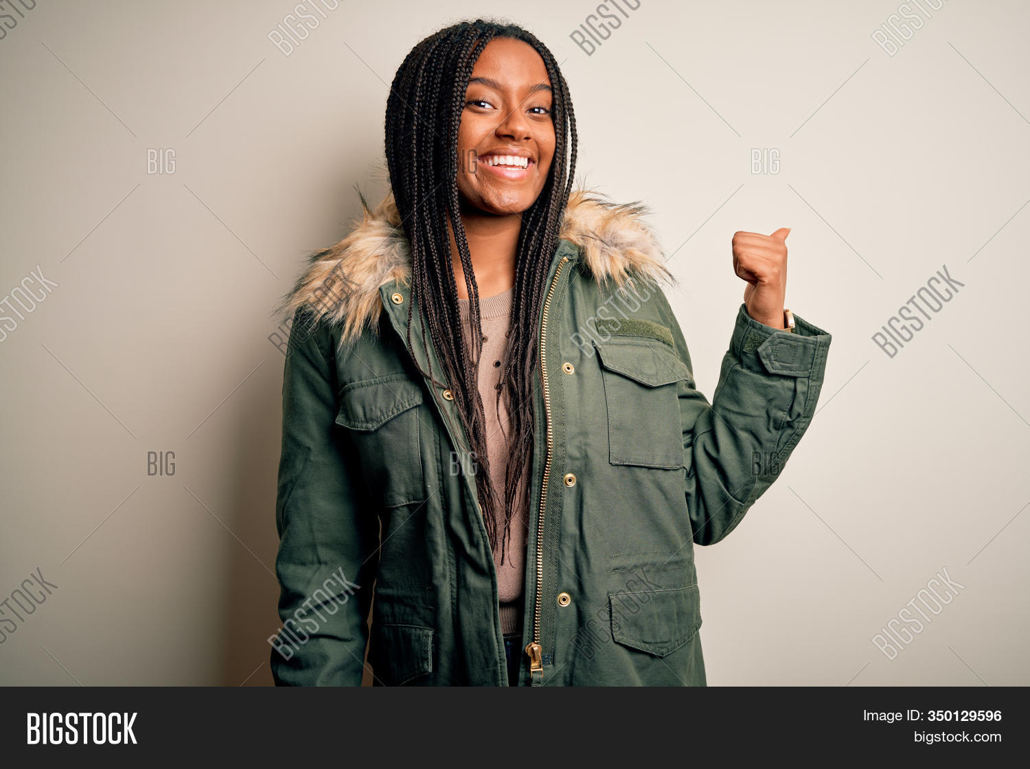 Young african american woman wearing winter parka coat over isolated background smiling with happy face looking and pointing to the side with thumb up.