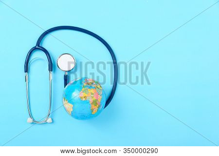 World Health Day Concept, Stethoscope, Globe On Blue Background With Copy Space. Global Health Care