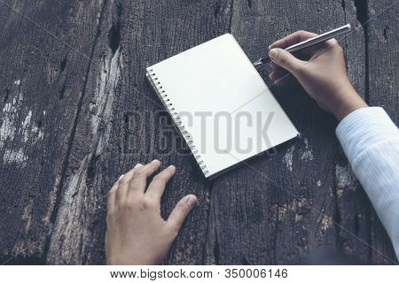 Close Up Woman Hand Writing On Notebook. Woman Writing On Note Paper Diary On Wooden Table.