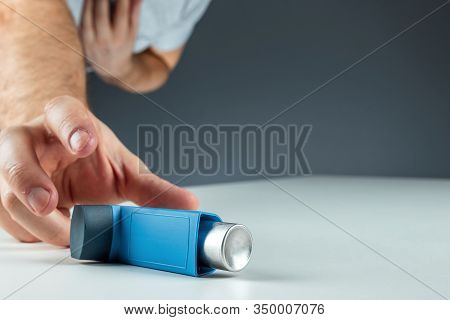 The Male Hand Reaches For An Asthma Inhaler, An Asthmatic Attack. The Concept Of Treatment Of Bronch