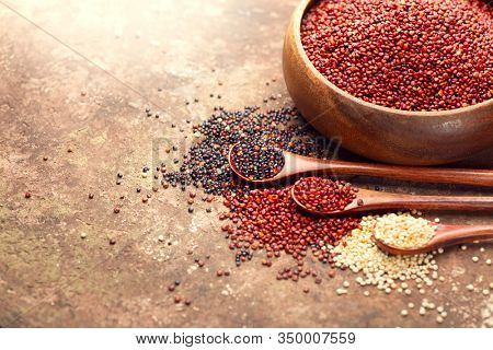 Red, black and white quinoa grains in a wooden spoon. Healthy food in a bowl. Seeds of white, red and black quinoa - Chenopodium quinoa. Diet, Dieting concept. Vegan food
