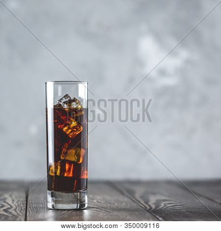 Glass Of Brew Cold Coffee And Ice. Cold Summer Drink On A Dark Wooden Table And Gray Background With