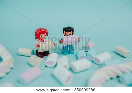 Lego Toy Hold Marshmallow. Colorful Marshmallow On Blue Background. Many Candies On The Table. Lego