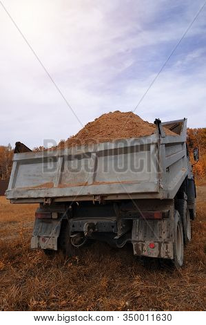 A Dump Truck Unloads Sand In The Construction Site.