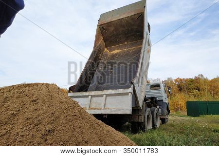 A Dump Truck Unloads Sand At A Construction Site To Mix Cement.