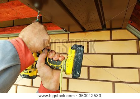 The Worker Measures The Length Of The Eaves Under The Roof.