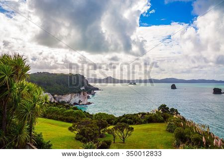 The road to Cathedral Cove. Lush clouds of strange shapes over picturesque exotic trees and bushes. New Zealand. Travel to the edge of the Earth. The concept of exotic and photo tourism