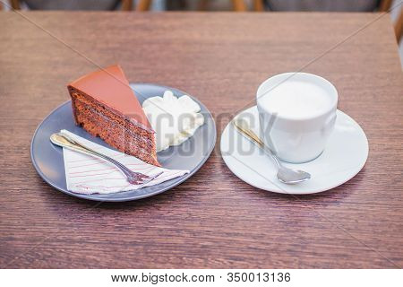 Classic Viennese Coffee. Dessert With Chocolate Cake With Whipped Cream On A Plate With A Spoon And