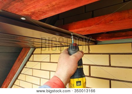 Workers Install Eaves Under The Roof Of The House.