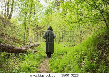 Man In Rain Coat Stand Back On Background Of Wet Forest. Healthy Lifestyle. Green Summer Nature. Man