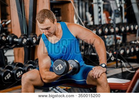 A Young Muscular Guy Does Hard Exercises With Dumbbells For The Rear Deltas Of The Shoulders On A Tr