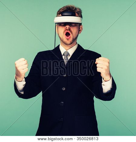 Businessman In A Formal Wear Wearing Virtual Reality Glasses Holding A Virtual Steering Wheel - Imag