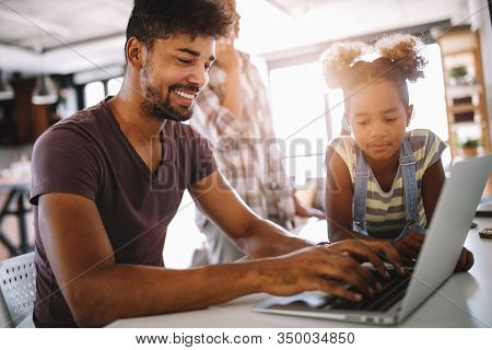 Father And Daughter Working On Laptop. Businessman Working From Home And Watching Child