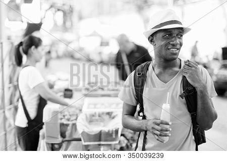 Young Happy African Tourist Man Thinking While Holding Bottle Of Orange Juice In The Streets