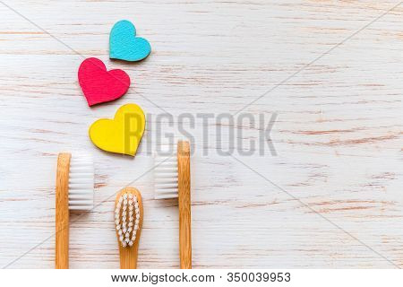 Family Set Of Bamboo Toothbrushes And Wood Hearts On Vintage Wood Background. Natural Products. Biod