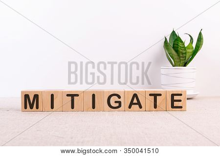 Mitigate Word Made With Building Blocks On A Light Background