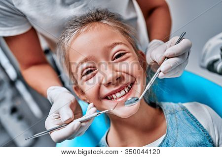 Hands Of Unrecognizable Pediatric Dentist Making Examination Procedure For Smiling Cute Little Girl