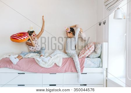 Two children playing together in bed, having fun in bright girly playroom. Kids paljamas party in white bedroom interior.